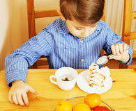 Petits garçons mignons mangeant le dessert sur la cuisine en bois Intérieur à la maison Photo libre de droits
