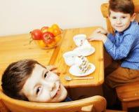 Petits garçons mignons mangeant le dessert sur la cuisine en bois Intérieur à la maison Photos stock