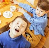 Petits garçons mignons mangeant le dessert sur la cuisine en bois Intérieur à la maison amis adorables de sourire d'amitié ensemb Photo libre de droits