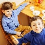 Petits garçons mignons mangeant le dessert sur la cuisine en bois Intérieur à la maison Images stock