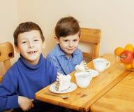 Petits garçons mignons mangeant le dessert sur la cuisine en bois Intérieur à la maison Photographie stock libre de droits