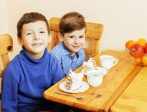 Petits garçons mignons mangeant le dessert sur la cuisine en bois Intérieur à la maison Image libre de droits