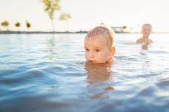 Petits garçons nageant dans l'eau le jour ensoleillé d'été Photos stock