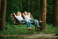Petits garçons rêvant sur l'oscillation Photographie stock