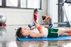 Petits garçons se trouvant sur le tapis de yoga et à l'aide du smartphone tandis qu'amis s'exerçant dans le gymnase Photos stock