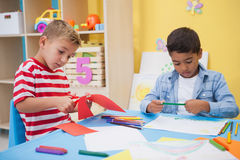 Petits garçons mignons dessinant au bureau Image stock