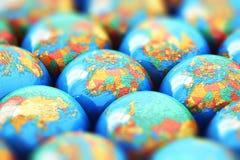 Petits globes de la terre avec des cartes du monde Photographie stock libre de droits