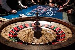 Petits groupes brillants en bois de roulette dans un casino et les gens Photo stock