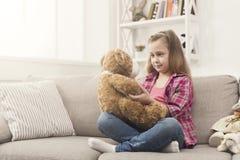 Petits heureux étreignant son nounours concernent le sofa photographie stock