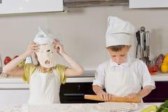 Petits jeunes garçons jouant tout en faisant cuire au four Image stock