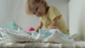 Petits jeux d'enfant avec des couches-culottes de bébé, fond, hygienics clips vidéos