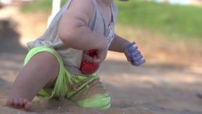 Petits jeux mignons de bébé sur la plage avec la palette, le râteau et le sable clips vidéos