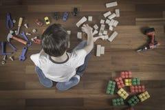 petits jouets de jeu de garçon Badinez se reposer sur le plancher en bois dans sa chambre Vue supérieure Photographie stock