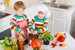 Petits jumeaux faisant cuire la soupe et le repas italiens avec les légumes frais Images stock