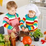 Petits jumeaux faisant cuire la soupe et le repas italiens avec les légumes frais Photos libres de droits