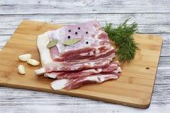 Petits morceaux coupés de ventre de porc avec l'ail et le poivre sur une planche à découper Morceaux juteux de lard avec le poivr images libres de droits