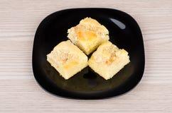 Petits morceaux de tarte dans le plat noir sur la table Photos stock