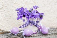 Petits oeufs et vase de pâques avec des violettes Images stock