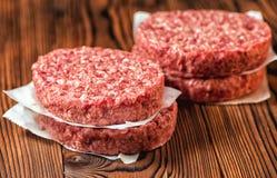 Petits pâtés crus d'hamburger de viande de boeuf haché sur le papier, photographie stock