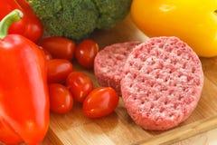 Petits pâtés crus de viande hachée sur un conseil en bois Photo stock