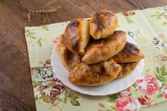 Petits pâtés russes avec le chou sur un plat et un beau fond Photos libres de droits