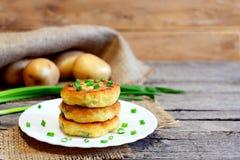 Petits pâtés végétaux rôtis Petits pâtés de pomme de terre avec des légumes et des épices de plat et sur la table en bois Pommes  Image stock