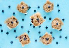 Petits pains avec des myrtilles sur le fond bleu Configuration plate image stock