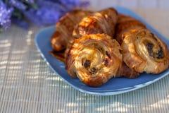 Petits pains avec des raisins secs et des croissants fran?ais d'un plat bleu Dessert photos libres de droits