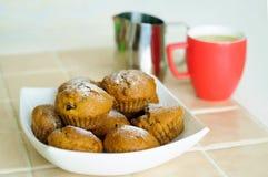 Petits pains avec du sucre en poudre sur un plateau et un broc de lait avec une tasse photographie stock