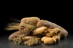Petits pains, baguette, ciabatta et pain sur la table en bois foncée Rye, orge, blé, avoine et beaucoup de pains mélangés frais s Photo stock