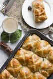 Petits pains croisés chauds avec la tasse de café, bâtons de cannelle sur la configuration d'appartement de table photos stock