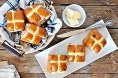 Petits pains croisés chauds de Pâques, scène aérienne sur le bois rustique Photo stock