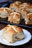 Petits pains croisés chauds de Pâques sur le fond foncé image libre de droits