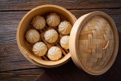 Petits pains cuits à la vapeur de porc dans le vapeur en bambou photos stock