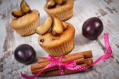 Petits pains cuits au four frais avec des prunes et des bâtons de cannelle sur le vieux fond en bois, dessert délicieux Photo libre de droits