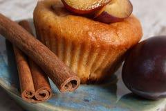 Petits pains cuits au four frais avec des prunes et des bâtons de cannelle sur le vieux fond en bois, dessert délicieux Image libre de droits