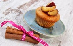 Petits pains cuits au four frais avec des prunes et des bâtons de cannelle sur le vieux fond en bois, dessert délicieux Image stock
