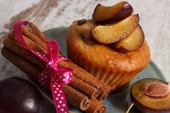 Petits pains cuits au four frais avec des prunes et des bâtons de cannelle sur le vieux fond en bois, dessert délicieux Images libres de droits