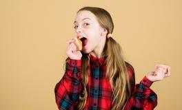 Petits pains d?licieux Enfant mignon de fille mangeant les petits pains ou le petit g?teau Dessert doux Recette culinaire Casse-c image libre de droits