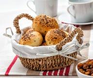 Petits pains dans un panier sur une table de petit déjeuner Image stock