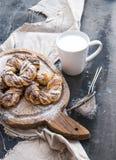 Petits pains de cannelle avec la poudre de sucre sur le panneau en bois rustique, tasse de lait, surface grunge foncée Photographie stock libre de droits