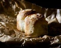Petits pains de cannelle classiques - cinnabons avec le givrage crémeux sur le papier de cuisson images stock