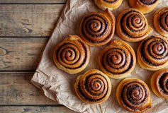 Petits pains de cannelle fraîchement cuits au four avec les épices et le cacao remplissant sur le papier parcheminé Cuisson faite Images libres de droits