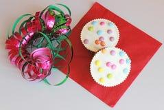 Petits pains de carnaval décorés des lentilles et des flammes colorées multi de chocolat photos stock