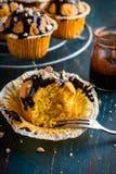 Petits pains de carotte avec l'écrimage et les écrous foncés de chocolat sur le dos de noir Image stock