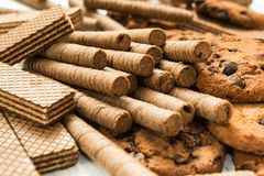 Petits pains de gaufre de chocolat, biscuits et gaufre classique sur une table blanche en bois Doux-toothers images libres de droits