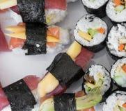 Petits pains de nigiri et de maki de sashimi de sushi, d'isolement sur le blanc Images stock