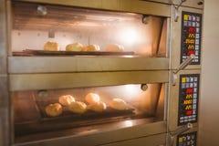Petits pains de pain faisant cuire au four en four Photos stock