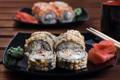 Petits pains de petit pain, de Californie de sushi de Philadelphie avec des bâtons, gingembre et wasabi de plat noir image stock