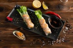 Petits pains de ressort asiatiques avec la crevette dans le plat rectangulaire noir image stock